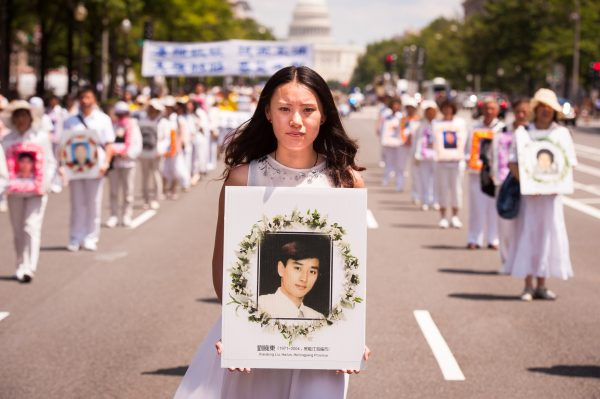 A women holds a photo of a fellow Falun Gong practitioner killed for his beliefs, during a parade calling for an end to the persecution in China, in Washington, D.C., on July 17, 2014. Today marks the 15th year of the persecution that began on July 20, 1999, in China. (Edward Dai/Epoch Times)