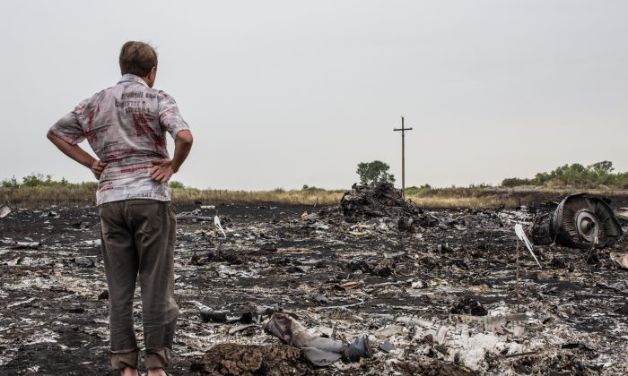 A man looks at debris from an Malaysia Airlines plane crash on July 18, 2014 in Grabovka, Ukraine. (Brendan Hoffman/Getty Images)