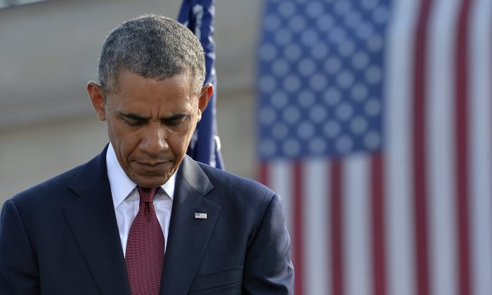 U.S. President Barack Obama bows his head during a ceremony at the Pentagon Memorial to mark the 12th anniversary of the 9/11 attacks in Washington, DC, on September 11, 2013. (Jewel Samad/AFP/Getty Images)