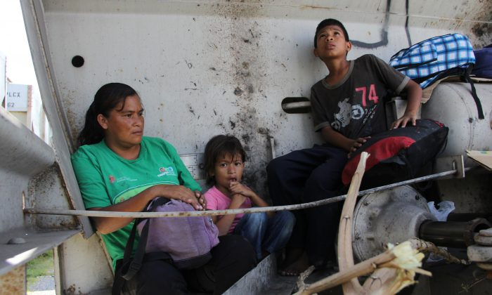 A Central American immigrant and her children sit inside the so-called La Bestia (The Beast) cargo train, in an attempt to reach the Mexico-US border, in Arriaga, Chiapas state, Mexico on July 16, 2014. (Elizabeth Ruiz/AFP/Getty Images)