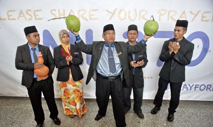 A well-known Malaysian malay bomoh (shaman), Ibrahim Mat Zin (C) holds two coconuts as him and his assistants offer to locate the missing Malaysia Airlines flight 370 plane using a spiritual method and prayer at the Kuala Lumpur International Airport (KLIA) in Sepang on March 12, 2014. Malaysia has expanded its search area for a missing jet after three days of scouring the sea failed to bring forth any confirmed sightings of wreckage, an official said. (MOHD RASFAN/AFP/Getty Images)