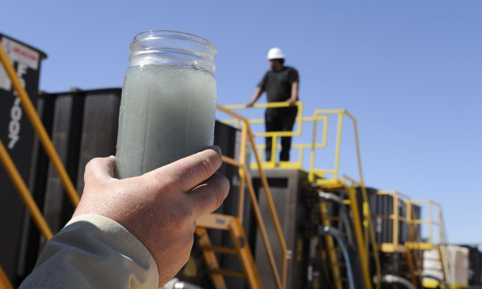 A jar holding waste water from hydraulic fracturing is held up to the light at a recycling site in Midland, Texas, Sept. 24, 2013. The drilling method known as fracking uses huge amounts of high-pressure, chemical-laced water to free oil and natural gas trapped deep in underground rocks. With fresh water not as plentiful companies have been looking for ways to recycle their waste. (AP Photo/Pat Sullivan)