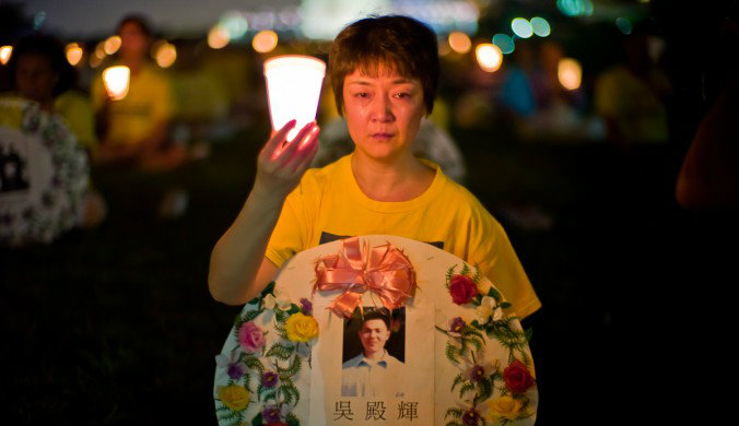 Falun Gong practitioner Jennifer Zeng cries as she honors a victim of the persecution, at the Washington Monument in Washington on July 22, 2010. (Mark Zou/Epoch Times)