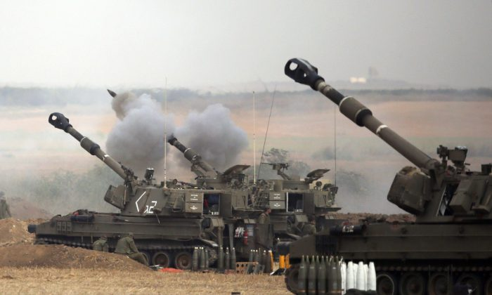 An Israeli artillery fires a 155mm shell towards targets in the Gaza Strip from their position near Israel's border with the Strip on July 20, 2014.  (Jack Guez/AFP/Getty Images)