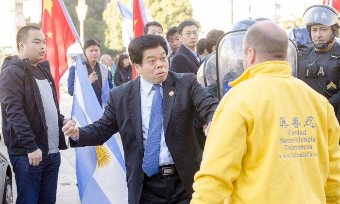 The president of the CASRECH (Chamber of Supermarkets and Self-Service Restaurants Owned by Chinese Residents in Argentina) threatens a Falun Gong practitioner in Buenos Aires, Argentina, on July 19, 2014. (Epoch Times)