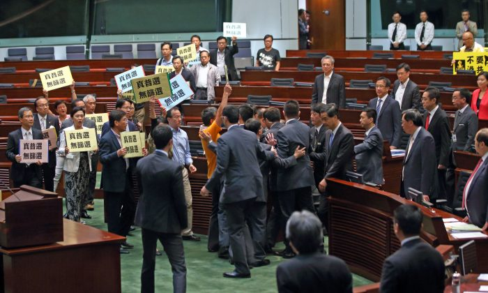 "Over 20 pan-democratic LegCo members collectively walk out to protest against Chief Executive Leung Chun-ying during Question and Answer Session in LegCo chamber on July 3, 2014. They are holding banners demanding for ""Genuine Universal Suffrage, No Screening."" (C.S. Poon/Epoch Times)"