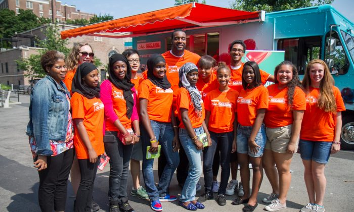 """NFL football player, Chris Canty (C), appears with administrators and teens from the Food Bank For New York City's EATWISE program, at Mullaly Park in the Bronx, on Monday, July 21, 2014. Canty, who plays with the Baltimore Ravens, was promoting the organization's latest campaign to encourage young teens to eat healthy, """"Change One Thing""""—replacing one unhealthy item in their diet. (Annie Wu/Epoch Times)"""