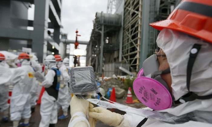 A Tokyo Electric Power Co.'s staff measures the radiation level as workers work on the construction of an ice wall at the tsunami-crippled Tokyo Electric Power Co.'s Fukushima Daiichi Nuclear Power Plant in Okuma, Fukushima Prefecture, northeast of Tokyo on July 9, 2014. Tokyo Electric Power Co. (TEPCO) will build a frozen ice wall around the buildings of Units 1 to 4 at the tsunami-devastated nuclear power plant to stop radiation-contaminated water from flowing to the sea. TEPCO has been struggling with massive amounts of toxic water as the operator continues to pump water into three reactors to keep them cool. The plant suffered meltdowns at three of its six reactors after a tsunami swept through the facilities in March 2011. (Kimimasa Mayama/AFP/Getty Images)