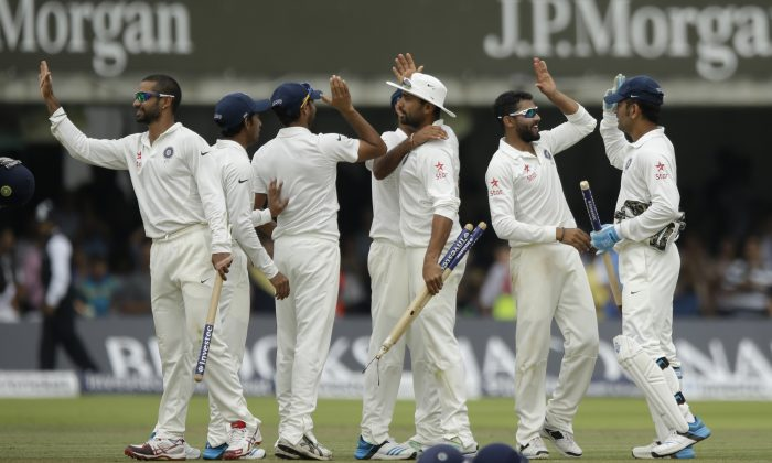 India's Ravindra Jadeja, second right, celebrates with his teammates including captain and wicketkeeper Mahendra Singh Dhoni, right, after running out England's James Anderson to win the test match on the fifth day of the second cricket test match between England and India at Lord's cricket ground in London, Monday, July 21, 2014. (AP Photo/Matt Dunham)