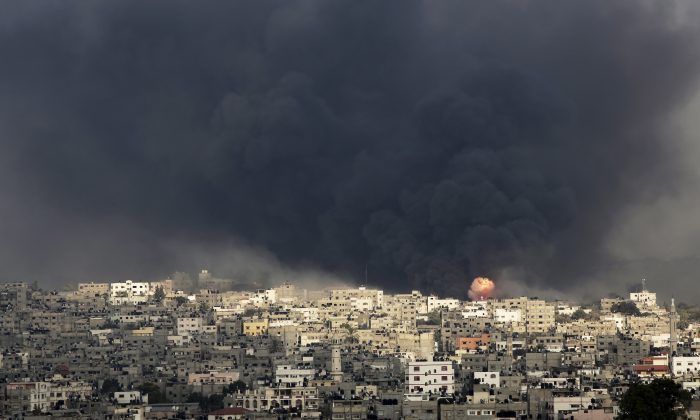 Smoke and flare of an explosion rise after an Israeli missile hit the Shijaiyah neighborhood in Gaza City, northern Gaza Strip, Sunday, July 20, 2014. The neighborhood came under heavy tank fire Sunday as Israel widened its ground offensive against Hamas, causing hundreds of panicked residents to flee. (AP Photo/Adel Hana)