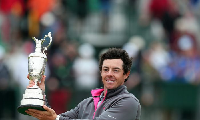 Northern Ireland's Rory McIlroy holds up the Claret Jug after winning the 2014 British Open Golf Championship at Royal Liverpool Golf Course in Hoylake. At 25, McIlroy joins legends Tiger Woods and Jack Nicklaus as the only players to have won three of the four majors by the time they were 25. (Andrew Yates/AFP/Getty Images)
