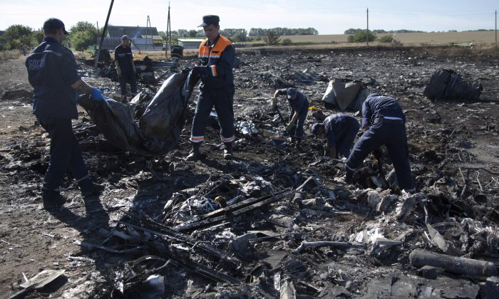 Ukrainian Emergency workers carry a victim's body in a plastic bag at the crash site of Malaysia Airlines Flight 17 near the village of Hrabove, Donetsk region, eastern Ukraine Monday, July 21, 2014. Another 21 bodies have been found in the sprawling fields of east Ukraine where Malaysia Airlines Flight 17 was downed last week, killing all 298 people aboard. (AP Photo/Dmitry Lovetsky)
