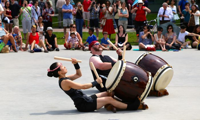 Two members of Oto-Wa Taiko play while sitting on the ground at the Japanese Summer Festival in Ottawa on July 19, 2014. (Pam McLennan/Epoch Times)
