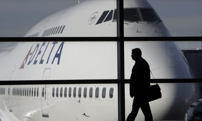 In this file photo made Jan. 21, 2010, a passenger walks past a Delta Airlines 747 aircraft in McNamara Terminal at Detroit Metropolitan Wayne County Airport in Romulus, Mich. Delta Air Lines on Tuesday, July 22, 2014 canceled all flights to Israel until further notice, citing reports that a rocket landed near Tel Aviv's Ben Gurion Airport. (AP Photo/Paul Sancya)