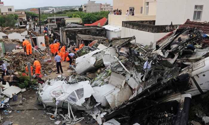 Rescue workers and firefighters search through the wreckage where TransAsia Airways flight GE222 crashed the night before near the airport at Magong on the Penghu island chain on July 24, 2014. Taiwan's TransAsia Airways said on July 24 that 48 people were killed and 10 survived when one of its turboprop passenger planes crashed after an aborted landing during stormy weather.  (Sam Yeh/AFP/Getty Images)