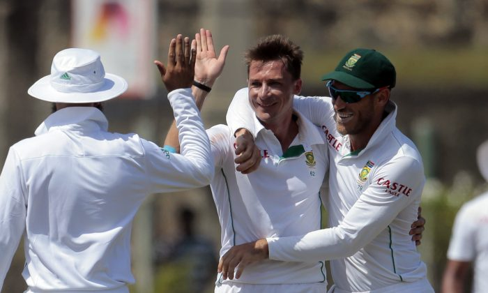 South African bowler Dale Steyn, center, celebrates taking the wicket of Sri Lankan batsman Kaushal Silva with team mates Hashim Amla, lef, and Faf du Plessis  during the fifth day of the first test cricket match between Sri Lanka and South Africa in Galle, Sri Lanka, Sunday, July 20, 2014. (AP Photo/Eranga Jayawardena)