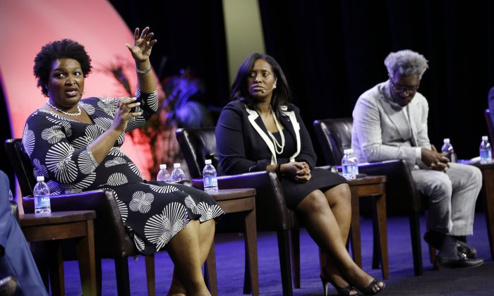 Stacy Abrams, (L), house minority leader for the Georgia General Assembly, on a panel with Jotaka Eaddy, (C), and Cornell Belcher, (R), on voter suppression during the NAACP annual convention July 22, 2014, in Las Vegas. (AP Photo/John Locher)