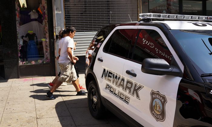 People walk by a police car in downtown Newark, N.J., May 13, 2014. (Spencer Platt/Getty Images)