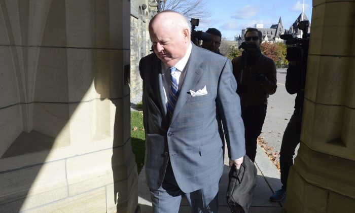 Sen. Mike Duffy walks to the Senate on Parliament Hill on Oct. 28, 2013. Now that Duffy has been formally charged, the Liberals are urging the ethics commissioner to re-open her investigation into the Senate expense scandal. (The Canadian Press/Adrian Wyld)