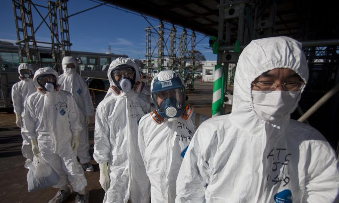 This Nov. 12, 2011, photo shows workers in protective suits and masks as they wait to enter the emergency operation center at the crippled Fukushima Dai-ichi nuclear power station in Okuma, Japan. (AP Photo/David Guttenfelder)