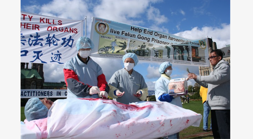 A re-enactment of organ harvesting in China on Falun Gong practitioners, during a rally in Ottawa, Canada, 2008. Recent evidence points to a new DNA organ transplant matching database consisting of data from DNA samples taken from Falun Gong practitioners outside of detention or prison. (Epoch Times)