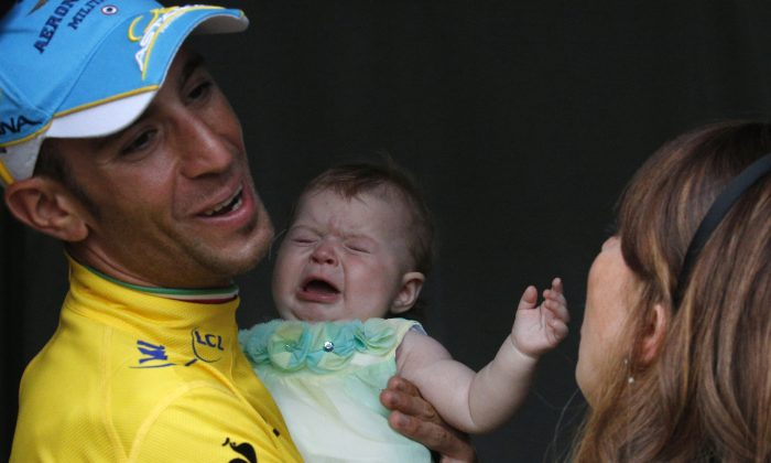 2014 Tour de France cycling race winner  Italy's Vincenzo Nibali laughs as his baby daughter Emma start to cry while waiting with his wife Rachele, right, for the team parade of the Tour de France cycling race in Paris, France, Sunday, July 27, 2014. (AP Photo/Christophe Ena)