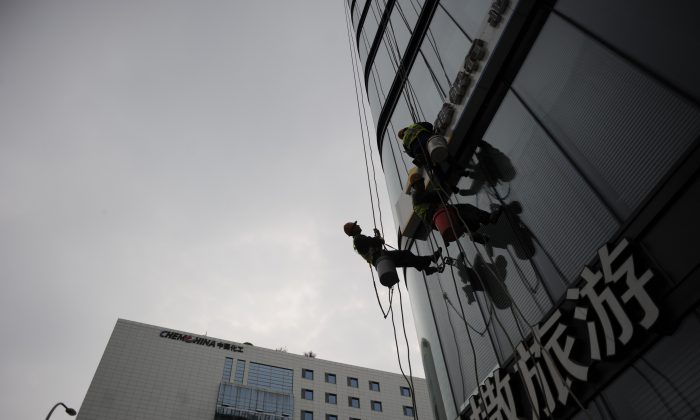 Chinese workers clean the decorative wall of a building in Beijing on April 16. (Wang Zhao/AFP/Getty Images)