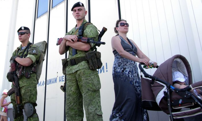 A woman pushes a baby in a stroller as she passes Ukrainian marines patrolling the Black Sea port of Odessa during Ukraine's Navy Day on July 27, 2014. (Alexey Kravtsov/AFP/Getty Images)