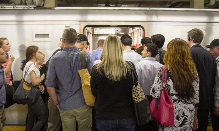 Commuters board a Long Island Rail Road train at Penn Station in Manhattan on July 17. (Benjamin Chasteen/Epoch Times)