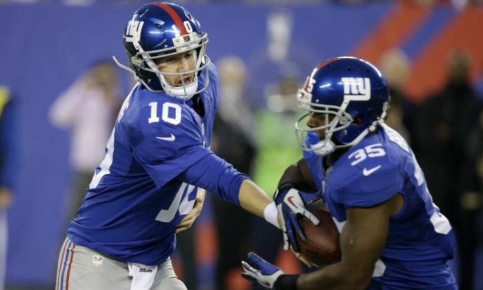 Giants quarterback Eli Manning hands off to Andre Brown (Sporting News)