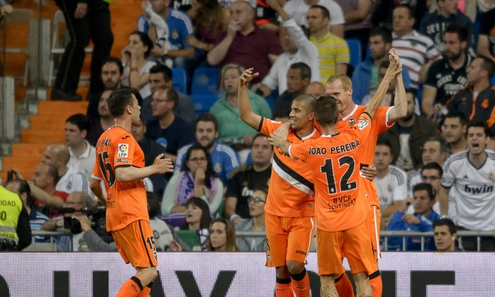 Valencia's French defender Jeremy Mathieu (R) celebrates with teammates after scoring during the Spanish league football match Real Madrid CF vs Valencia CF at the Santiago Bernabeu stadium in Madrid on May 4, 2014. The game ended in a draw 2-2. (DANI POZO/AFP/Getty Images)