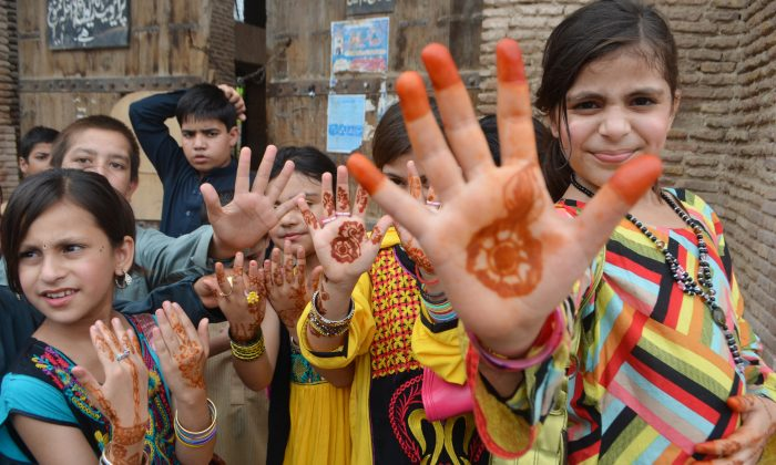 Pakistani girls show their hands painted with henna ahead of the Muslims Eid al-Fitr holiday that marks the end of the fasting month of Ramadan in Peshawar, Pakistan, Monday, July 28, 2014. (AP Photo/Mohammad Sajjad)