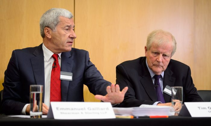 Emmanuel Gaillard of legal firm Shearman and Sterling LLP (L) speaks with as Tim Osborne (R), the CEO of GML Limited (formerly a shareholder in oil giant Yukos) looks on during a press conference in central London, England, on July 28, 2014. (Leon Neal/AFP/Getty Images)