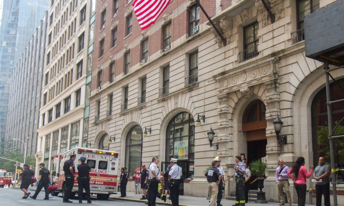 Fireman, policeman, and staff from the building where a fire broke out stand outside the building making sure the scene is secure, on 28th Street in Midtown Manhattan, New York, on July 29, 2014. (Benjamin Chasteen/Epoch Times)