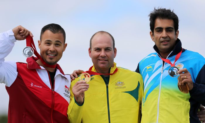 Australia's Adam Vella, center, celebrates winning the gold medal in the Trap Men with silver medalist Aaron Heading, left, and bronze medalist India's Manavjit Singh Sandhu at the Barry Budden Shooting Centre, during the 2014 Commonwealth Games in Carnoustie, Scotland, Tuesday July 29, 2014. (AP Photo/PA, Gareth Fuller)