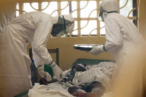 In this 2014 photo provided by the Samaritan's Purse aid organization, Dr. Kent Brantly, left, treats an Ebola patient at the Samaritan's Purse Ebola Case Management Center in Monrovia, Liberia. (AP Photo/Samaritan's Purse)