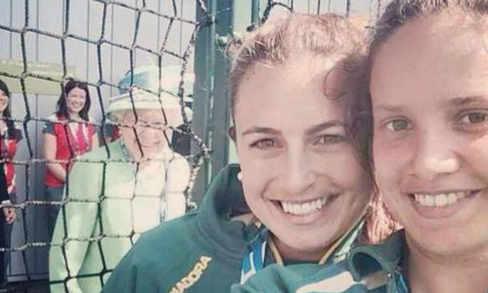 Hockeyroos Jade Taylor and Brooke Peris hit the jackpot when they took a 'selfie' at the Commonwealth Games in Glasgow on Thursday July 24, 2014. Hoping to catch the Queen in the background of a 'selfie' photo as she emerged from a doorway, Queen Elizabeth II immediately aware of what was happening made a broad smile at the smart phone. (Jade Taylor and Brooke Peris)