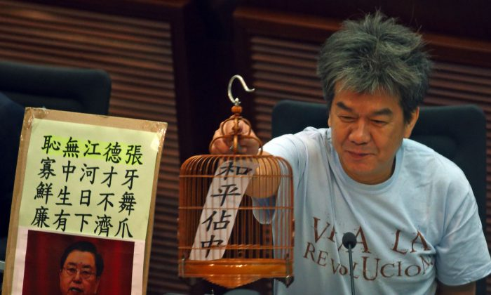 "Legislative councilor Leung Kwok-hung puts out a birdcage prop to satirize the Chinese and Hong Kong governments' giving Hong Kong people a ""birdcage constitutional reform,"" in the LegCo chamber on July 21. (Epoch Times)"
