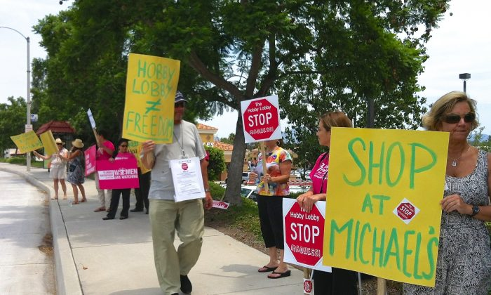 A group of protesters stands along the street outside of a business complex with a Hobby Lobby in Laguna Niguel, Calif., on July 29. (Sarah Le/Epoch Times)
