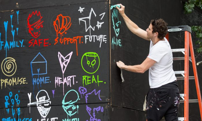 Gregory Siff paints a mural to kick off the partnership between The New York Foundling and COFFEED, on July 16. (Ryan Lash Photography)