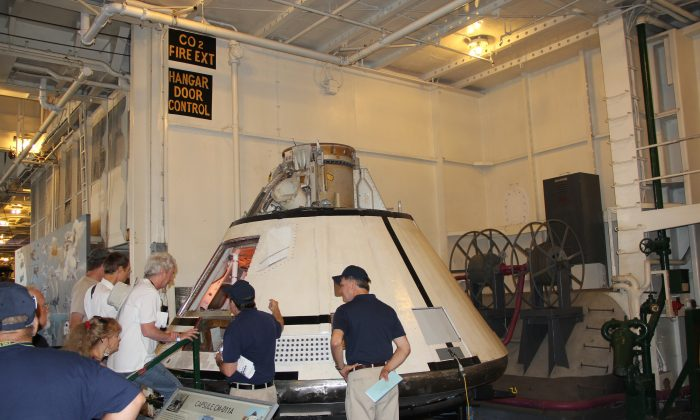"""Visitors look at the lunar module or """"capsule CM-011A"""" during the """"Splashdown 45"""" event aboard the USS Hornet in Alameda, Calif., on July 26. (Steve Ispas/Epoch Times)"""