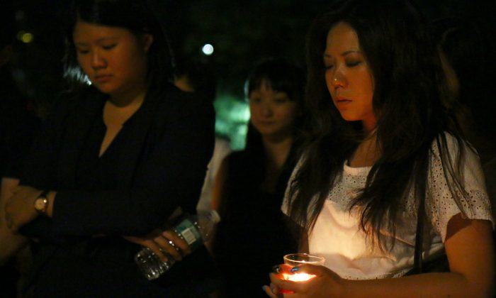Members of the local Malaysian community mourn lives lost in the flight MH17 disaster, at Washington Square Park, Manhattan, New York, July 21, 2014. (Brendon Fallon/Epoch Times)