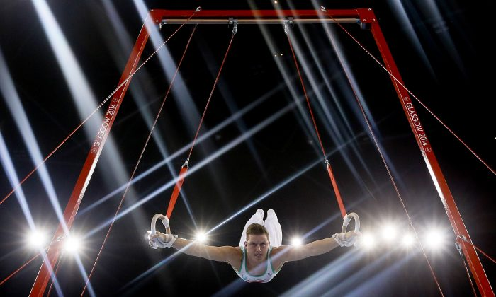 AUG 1 Lights flare as Harry Owen of Wales performs on the rings during the Men's All-Around gymnastics competition at the Scottish Exhibition Conference Centre during the Commonwealth Games 2014 in Glasgow, Scotland, on July 30, 2014. (AP Photo/Kirsty Wigglesworth)