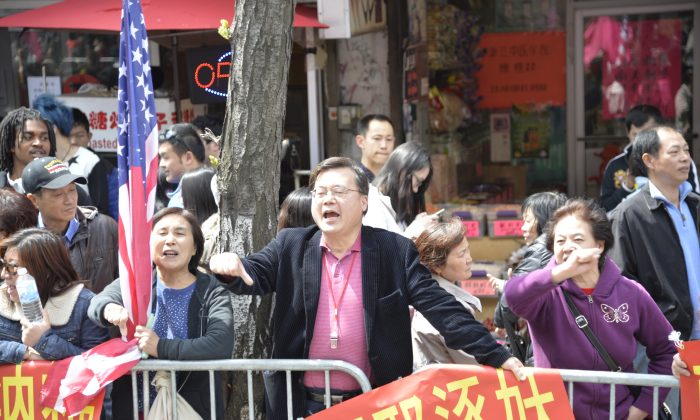 Micheal Chu yells and curses at Falun Gong practitioners during a parade in Flushing, Queens, New York City, on April 26, 2014. Chu heads an organization devoted to harassing practitioners. (Gary Du/Epoch Times)