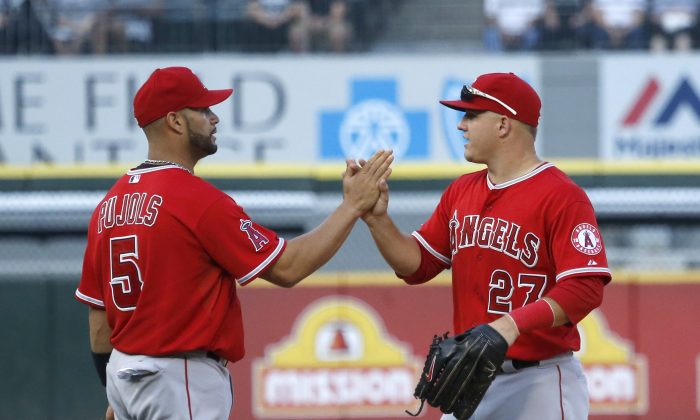 Los Angeles Angels center fielder Mike Trout (27) and Albert Pujols celebrate the Angels' 8-4 win over the Chicago White Sox after a baseball game Tuesday, July 1, 2014, in Chicago. (AP Photo/Charles Rex Arbogast)