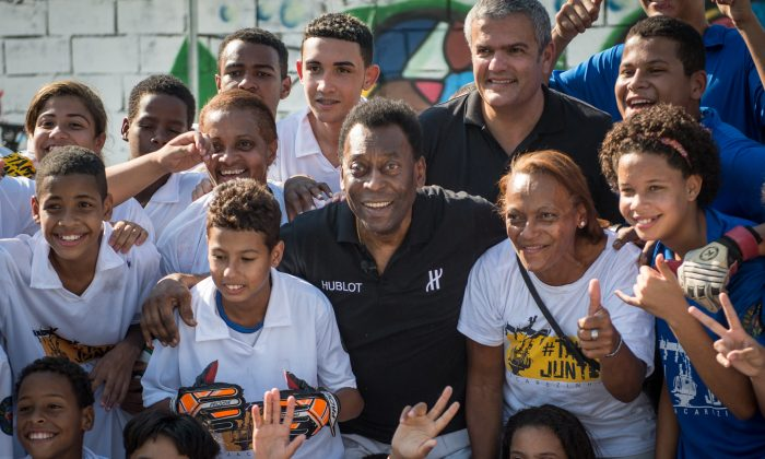 Brazilian former football star Pele (C) poses with children during the inauguration of a football pitch donated by Switzerland's watch company Hublot at Jacarezinho shantytown in Rio de Janeiro, Brazil on June 27, 2014. (YASUYOSHI CHIBA/AFP/Getty Images)