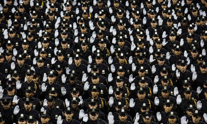 JULY 1: The 2014 class of the New York Police Department (NYPD) raise their hands while taking an oath at the NYPD graduation ceremony at Madison Square Garden in New York City, June 30, 2014. The NYPD, which has over 35,000 officers, graduated 604 new officers yesterday. (Andrew Burton/Getty Images)