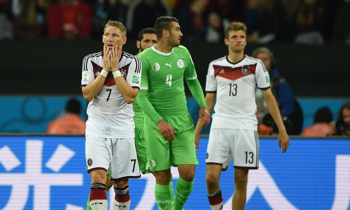 Germany's midfielder Bastian Schweinsteiger (L) reacts after missing a free-kick during a Round of 16 football match between Germany and Algeria at Beira-Rio Stadium in Porto Alegre during the 2014 FIFA World Cup on June 30, 2014. (KIRILL KUDRYAVTSEV/AFP/Getty Images)