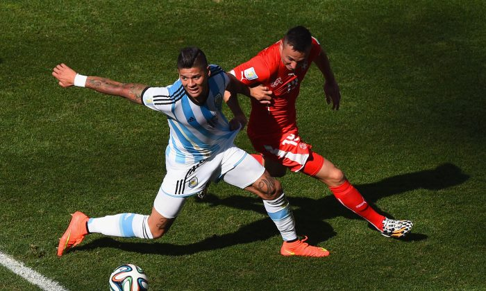 Josip Drmic of Switzerland challenges Marcos Rojo of Argentina during the 2014 FIFA World Cup Brazil Round of 16 match between Argentina and Switzerland at Arena de Sao Paulo on July 1, 2014 in Sao Paulo, Brazil. (Matthias Hangst/Getty Images)