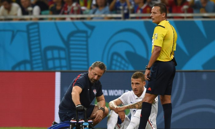 US defender Fabian Johnson (C) is treated by medical staff during a Round of 16 football match between Belgium and USA at Fonte Nova Arena in Salvador during the 2014 FIFA World Cup on July 1, 2014. (FRANCISCO LEONG/AFP/Getty Images)